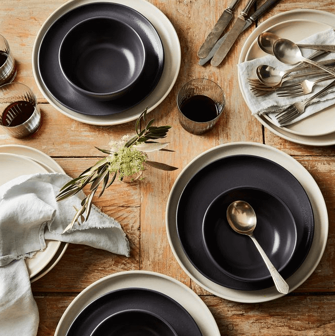 Table with matte black and white dishware on it