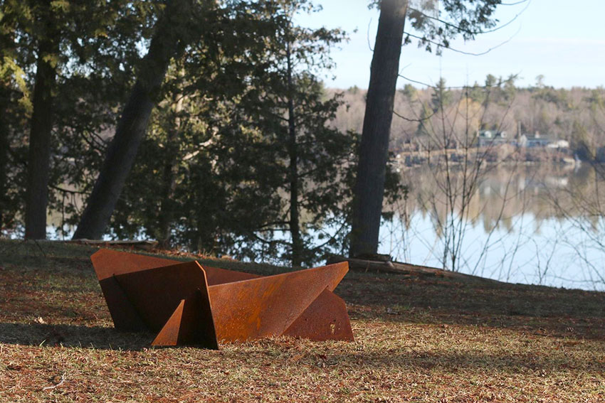 rusted geometric designed fire pit by the lake