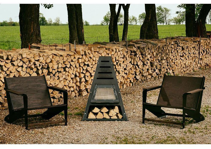 pyramid shaped iron fire pit in between two modern black chairs