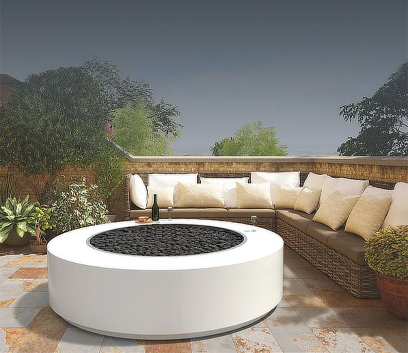white round modern fire pit at the center of an outdoor seating area