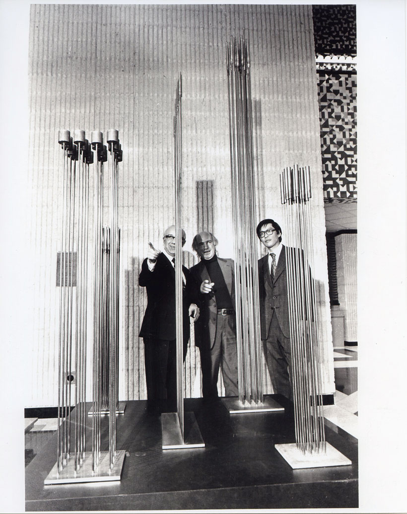 Three men admire the thin, vertical sound structures of Harry Bertoia's work