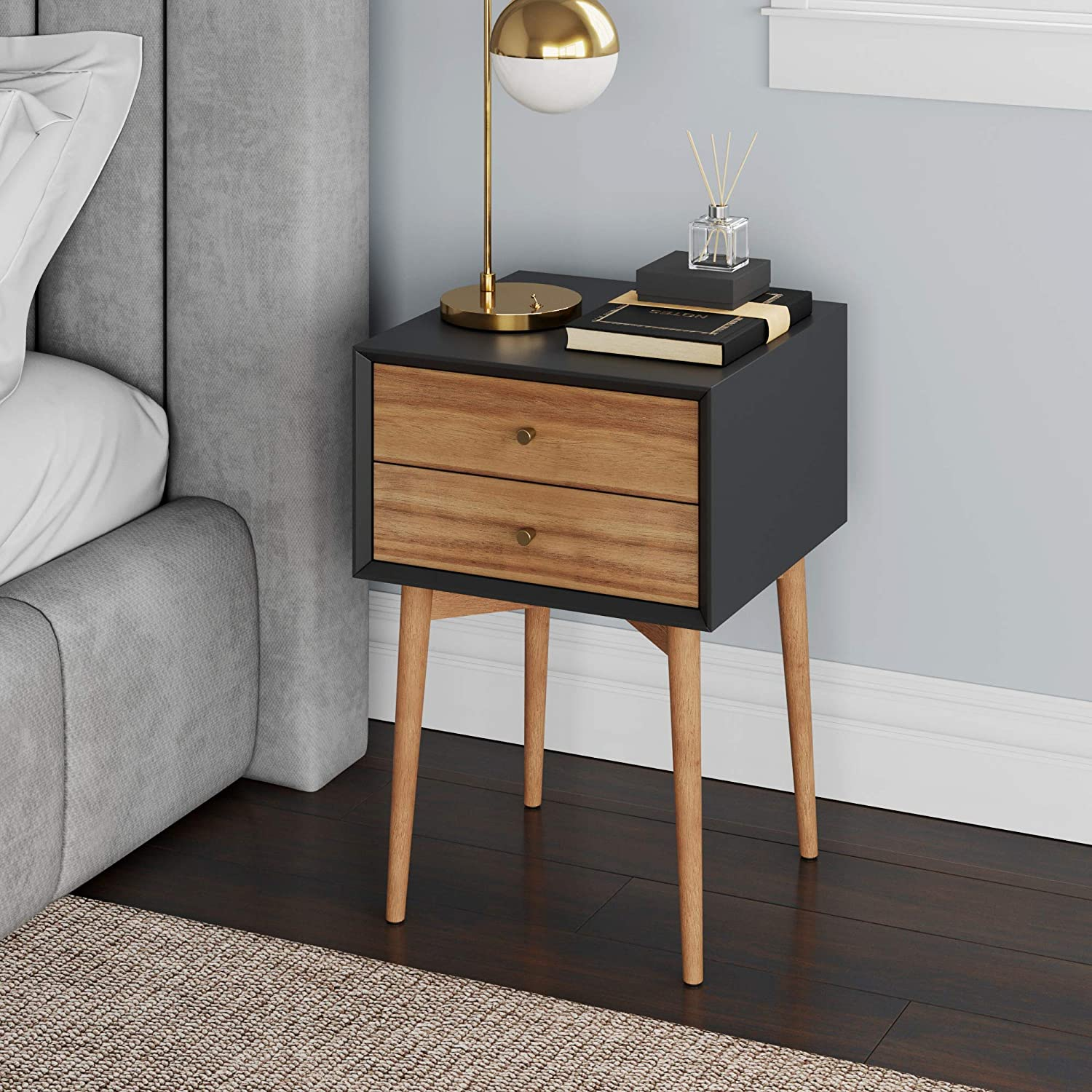 Wooden retro nightstand with long tapered legs and a natural finish except for the black top and sides.