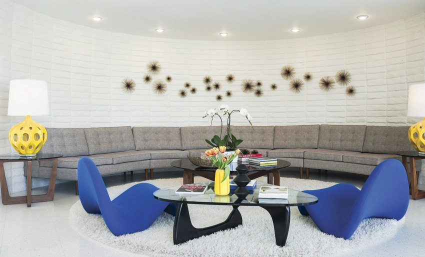 The mid century vacation home living room has a long, curved sofa against a white brick wall. Metal sunbursts decorate the wall while blue tongue chairs flank a modern coffee table.