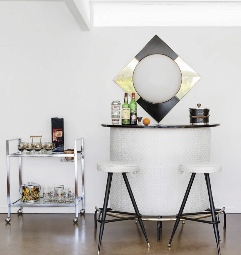 A small bar station has two stools and a retro bar cart.