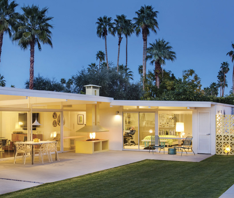 The backyard is lit by light coming through the retro Palm Springs home's floor to ceiling windows.