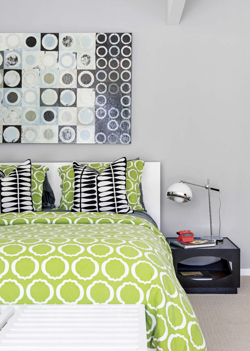 A lime green bedspread with gray walls and an abstract modern artwork.