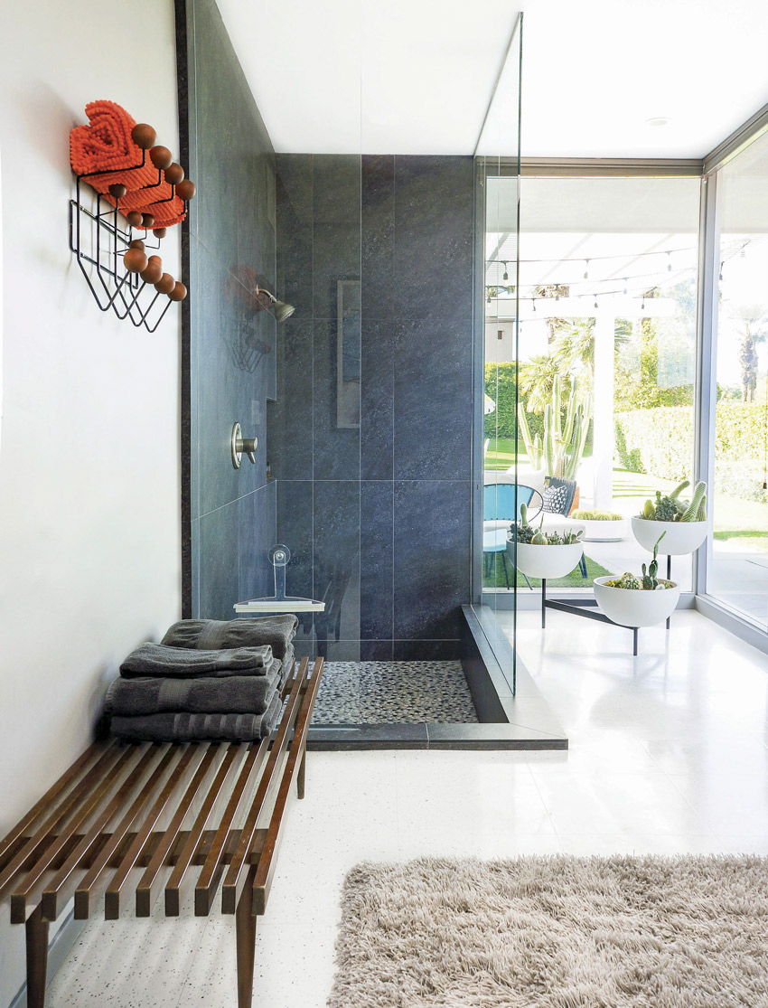 The mid century vacation home bathroom has a stone shower with glass walls, a slatted wood bench and three-tiered plant pot vessel.