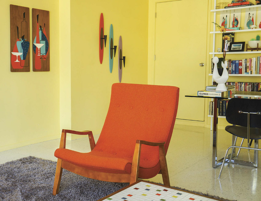 An orange scoop lounge chair sits atop a gray, shaggy area rug in a yellow room.