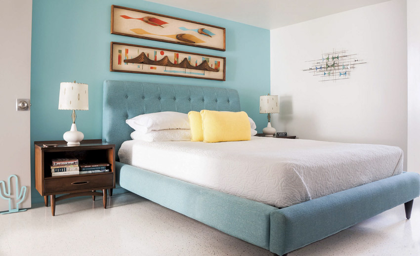 Guest bedroom in with a teal accent wall behind the bed's tufted headboard.