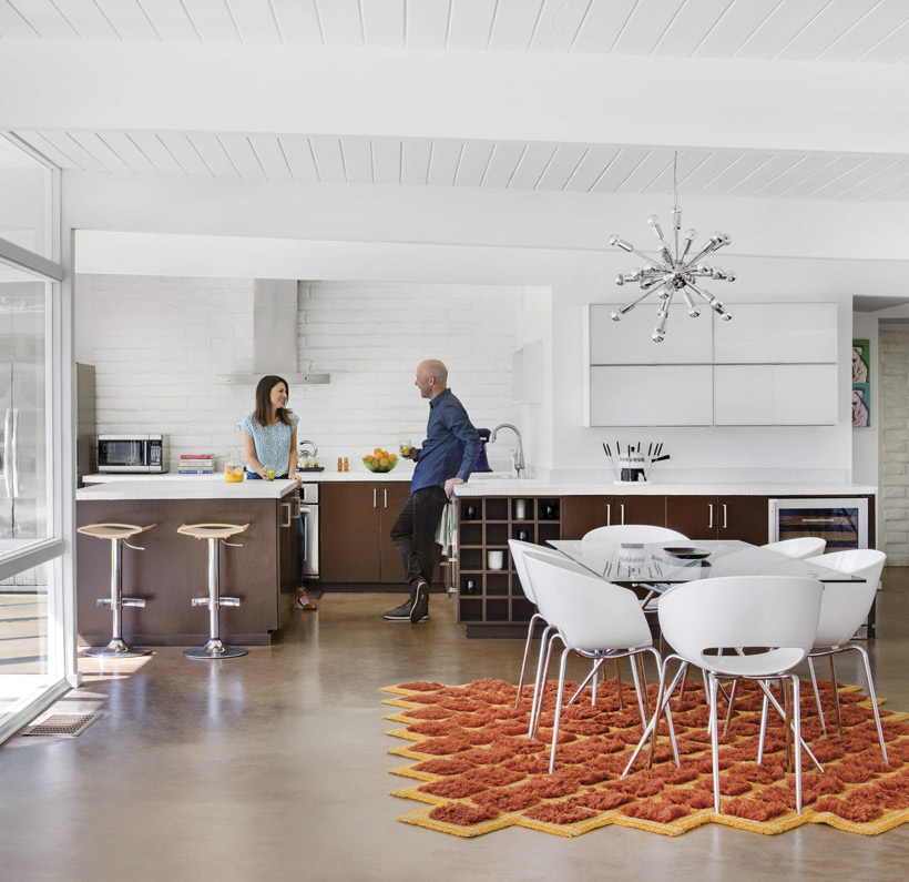 The couple chat in their minimalist retro Palm Springs kitchen.
