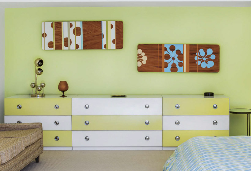 A large 9-drawer dresser has alternating white and green drawers in front of a light green wall.