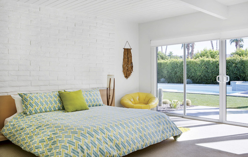 A large bed with a teal patterned bedspread has a white brick accent wall.