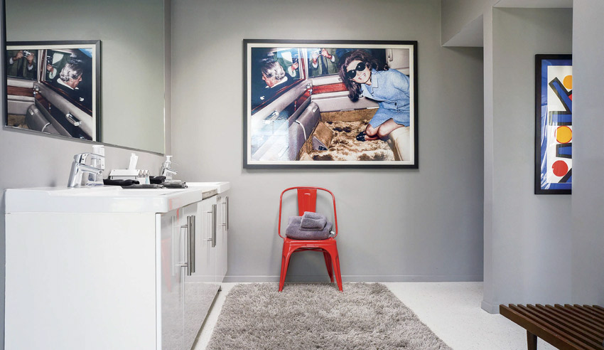 The master bathroom is gray with retro artwork, white cabinetry and an orange accent chair.