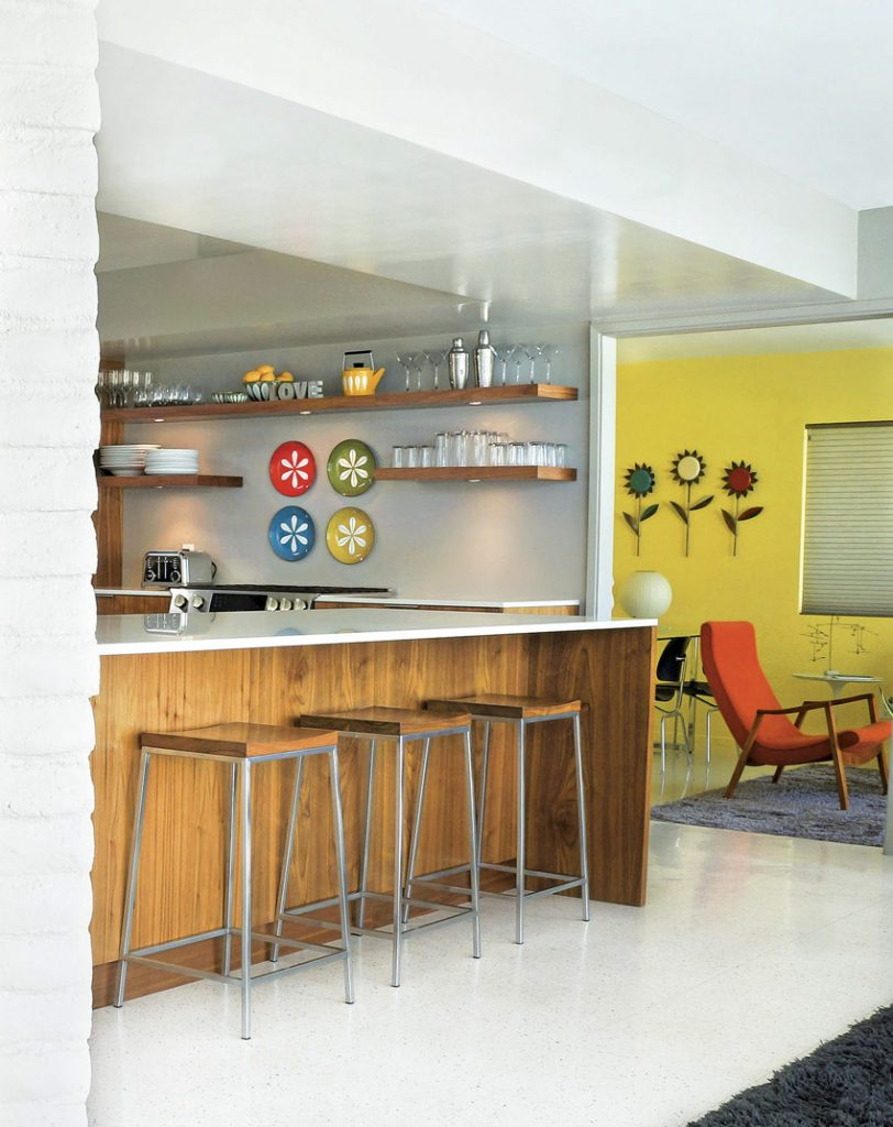 Beyond the kitchen, an open entryway leads to the yellow living room with scoop-back orange chairs.