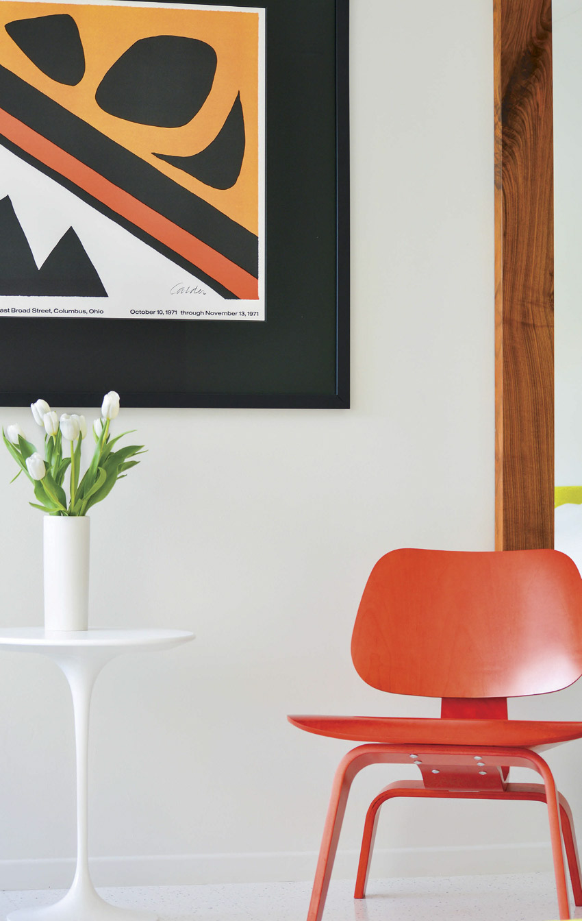A modern orange chair and white retro table sit in front of an abstract wall art piece.