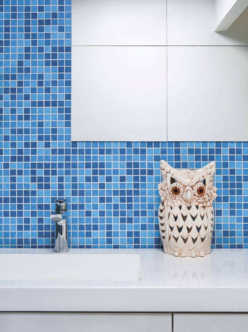 The bathroom tiling is multiple shades of blue and has a retro owl statue on the counter.