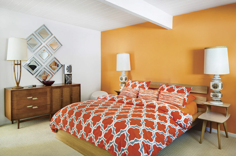 A bedroom with an orange accent wall and two large retro lamps flanking the orange bedspread.