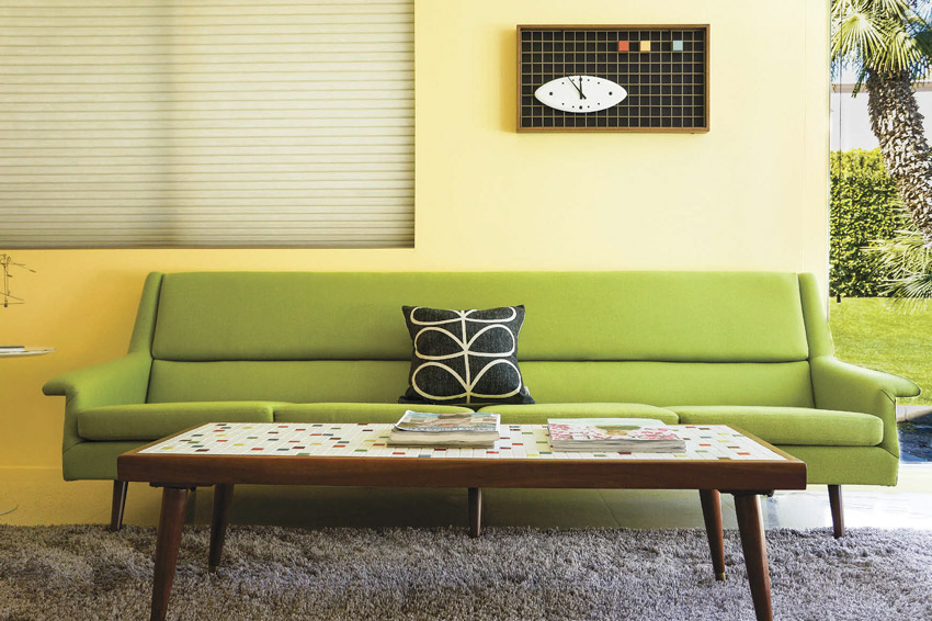 A lime green sofa rests in front of a yellow wall and above a gray, shaggy area rug.