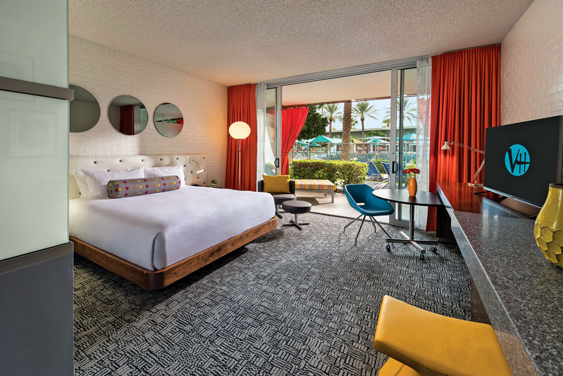 Neutral retro hotel room with a patterned carpet and dark orange curtains.