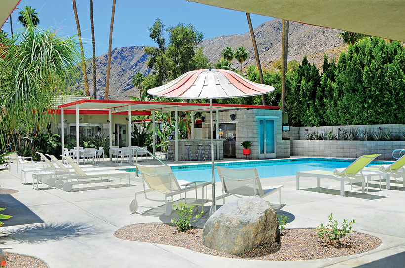 The small rectangular pool has poolside seating and surrounding greenery.