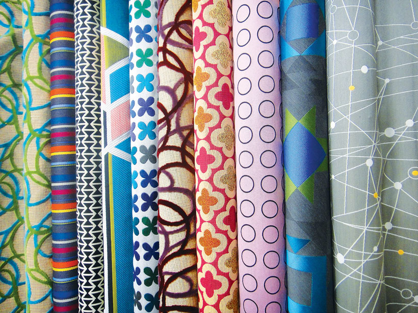 A variety of colorful fabrics rolls with mid century fabrics.
