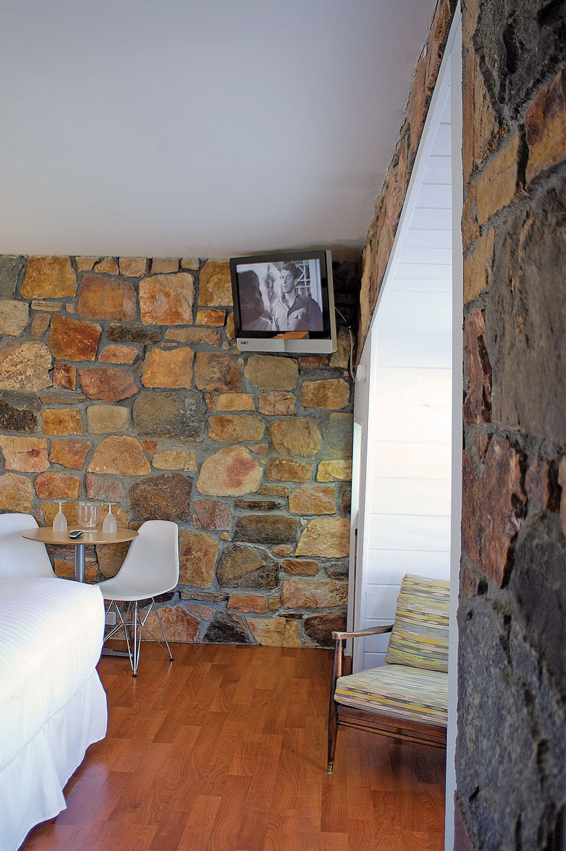 A small corner TV plays old classics above an indoor exposed stone wall.