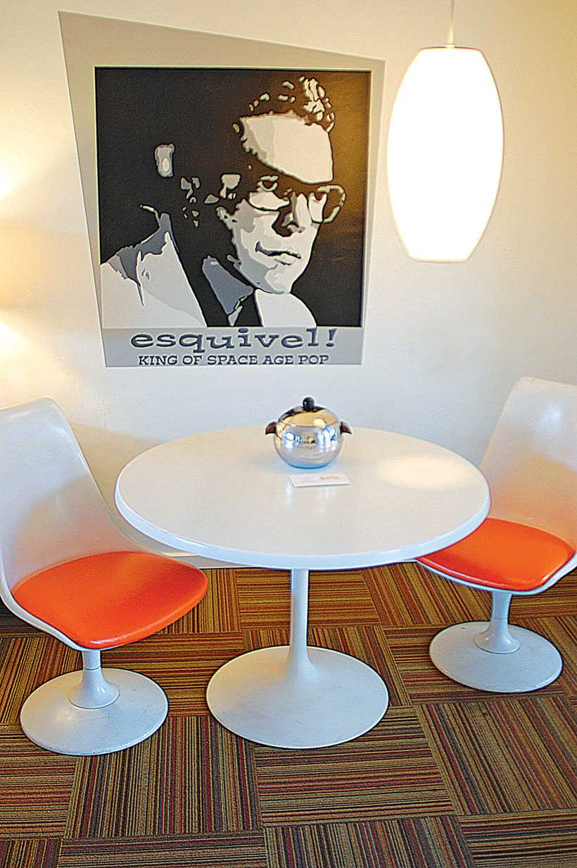 A black and white poster hangs above a round breakfast table with matching modern chairs.