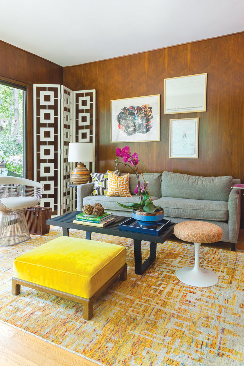 Living room furniture set with wood walls, statement art pieces and a large area rug.