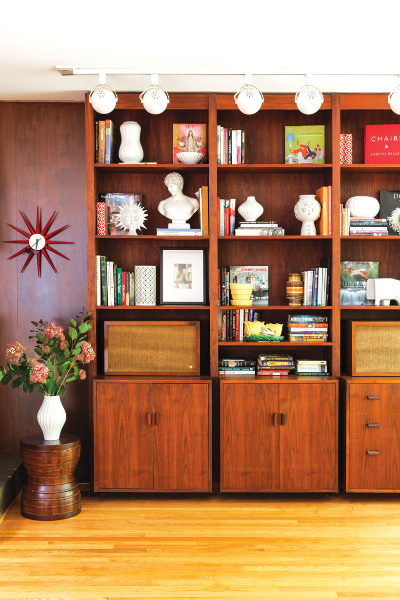 A mid century modern wooden bookcase boasts a collection of vintage mid century finds.