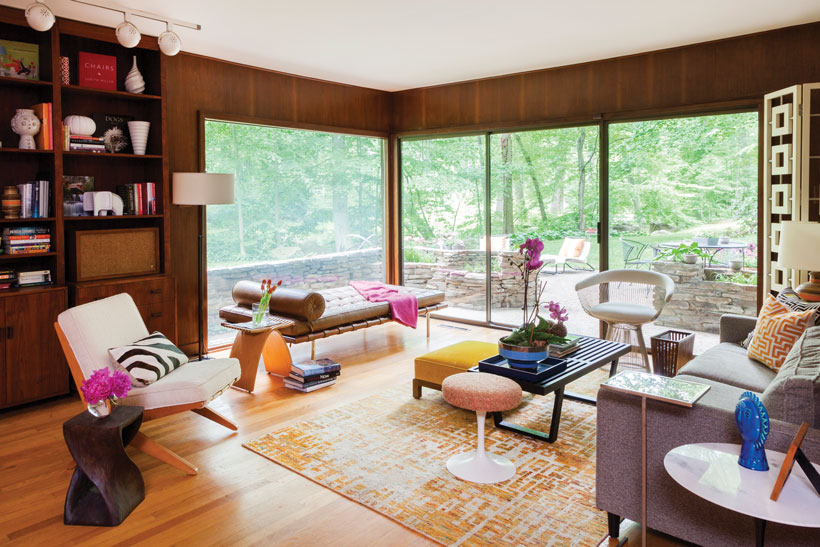 The house den with a variety of mid century modern furniture around a coffee table and area rug.