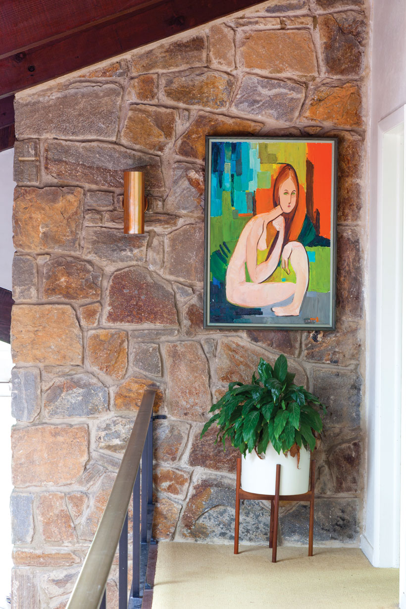 The side wall of the stone fireplace is connected to the upper level and sports an abstract painting hung above a raised plant.