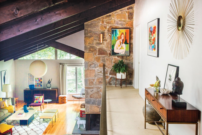 The upstairs hallway is connected to the stone fireplace and has a wood side table below a metal wall art piece.