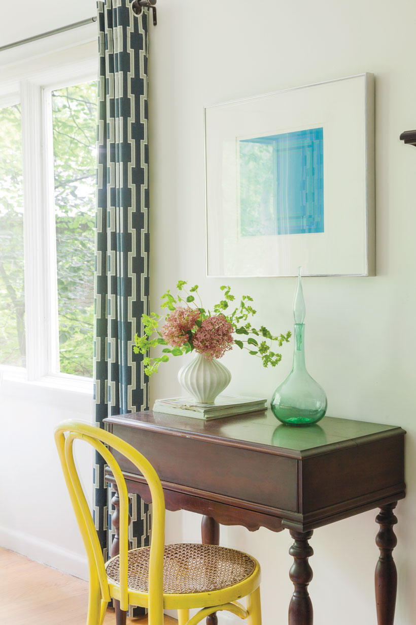 A small side table with a hand-painted yellow chair is beside a window with paneled curtains creates a vintage mid century look..