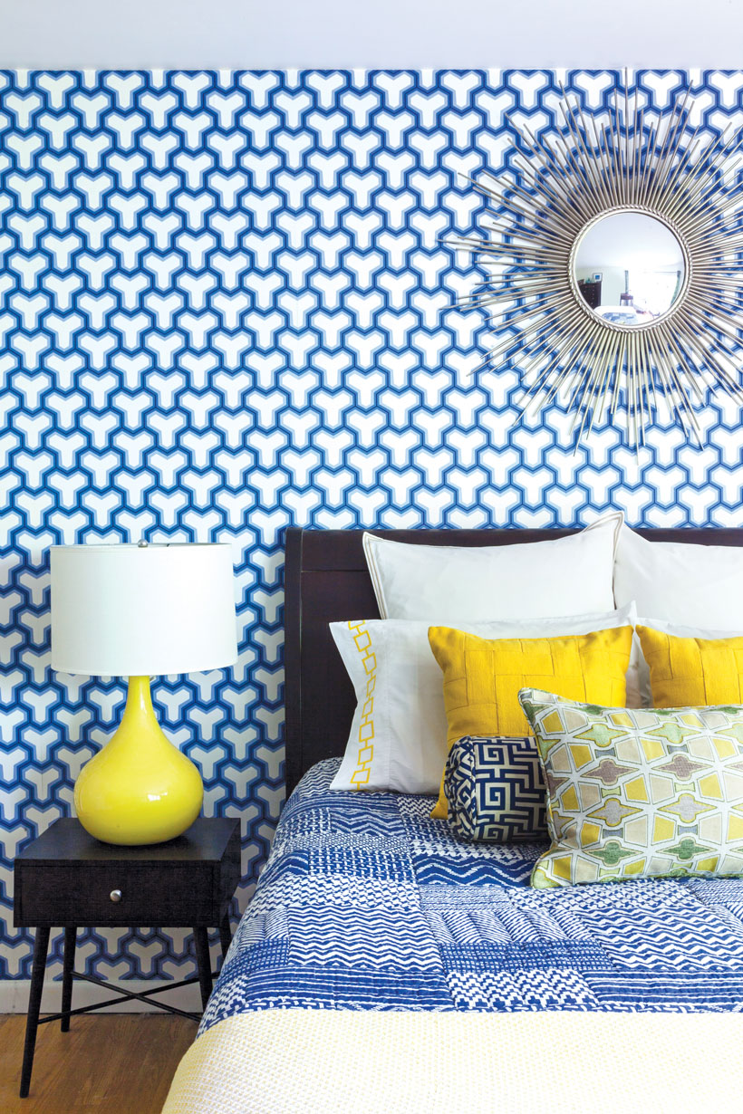 The guest pattern has bright blue patterned wallpaper and yellow accents on the bed and side table.