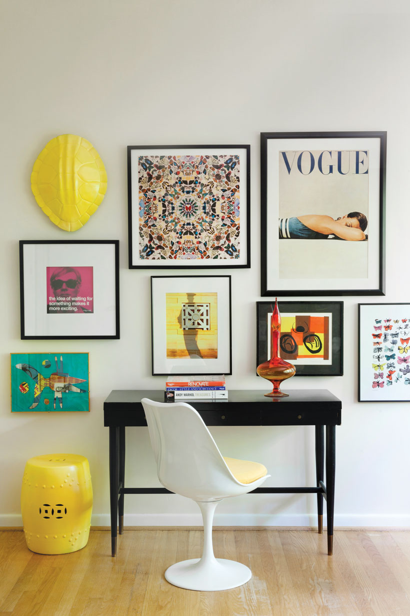 A side desk is surrounded by a mix of modern and vintage framed wall art, including a vintage mid century Vogue poster.