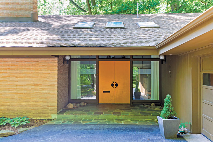 The front entrance has a stone veranda and wide double doors framed by large rectangle windows.