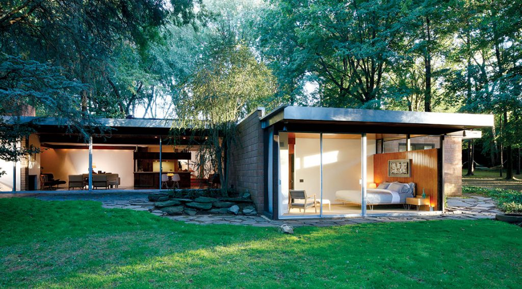 Exterior shot of a flat-roofed Mid Century Modern ranch with floor-to-ceiling windows, surrounded by forestry.