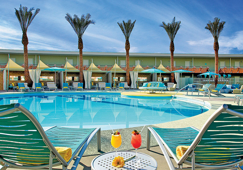 Palm trees and retro hotel umbrellas surround the side of a large round hotel pool.