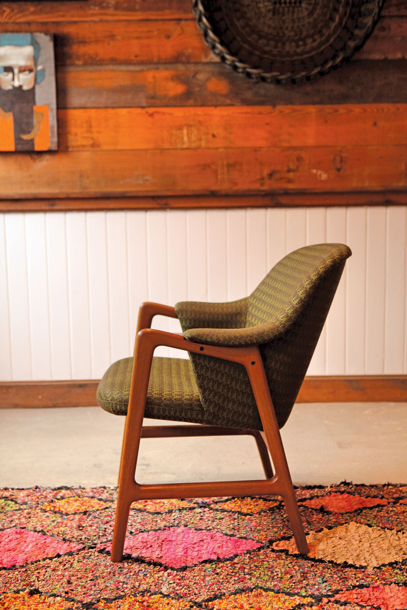 Olive green mid century chair with wooden legs.