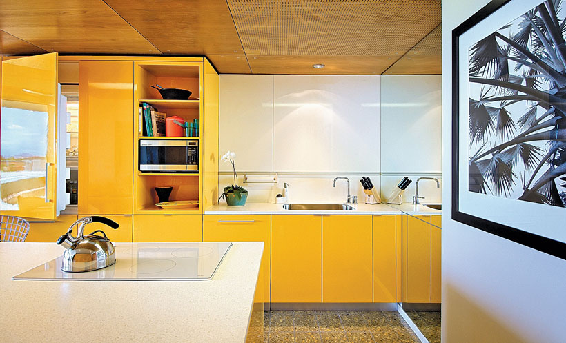 A hotel room's kitchenette has bright yellow cabinets and off-white counters.
