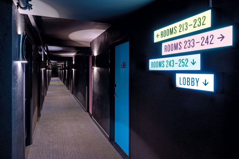 Four small neon signs direct guests to their room numbers in a dark hotel hallway with bright blue doors.