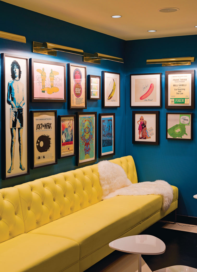 Tufted yellow couch in front of a blue accent wall with a gallery of framed, mid century art pieces.