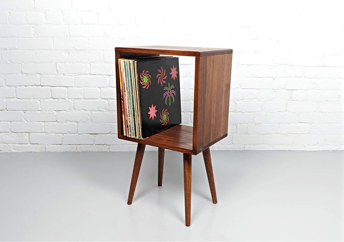 Naturally finished red wood nightstand with a large open box shelf on tapered legs.