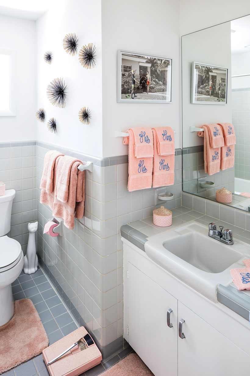 The bathroom has gray tiling, metal starbursts in the walls and matching pink his and hers hand towels.