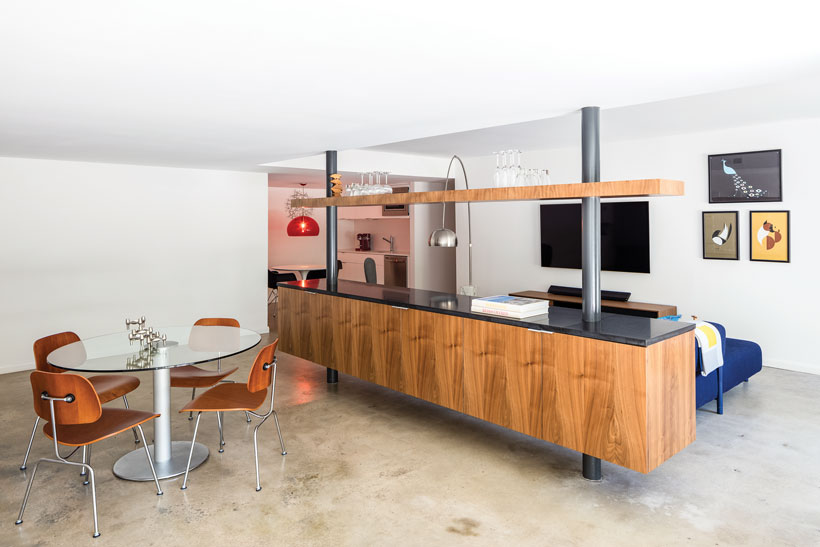 After the mid century renovation, the basement has polished concrete floors and a floating bar beside a glass dining table.