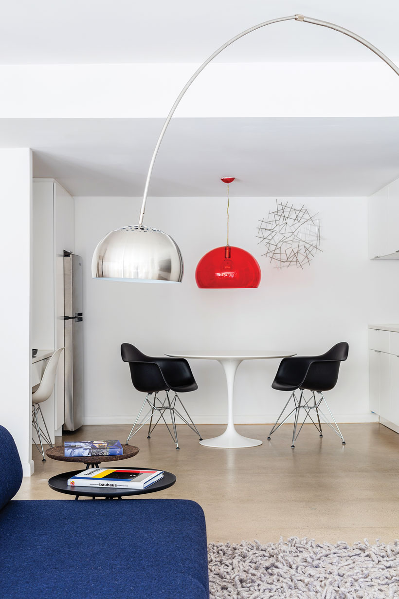The dining nook has a round white table, two black chairs and a bright red hanging lamp.