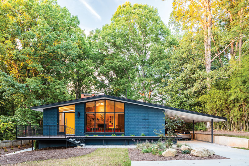 The home's dark turquoise exterior surrounded by trees.