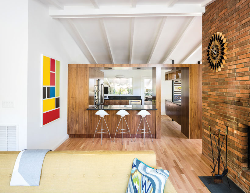 The mid century renovation opened the living room and the kitchen, complete with wood floors, retro white bar stools and a colorful modern wall art piece.