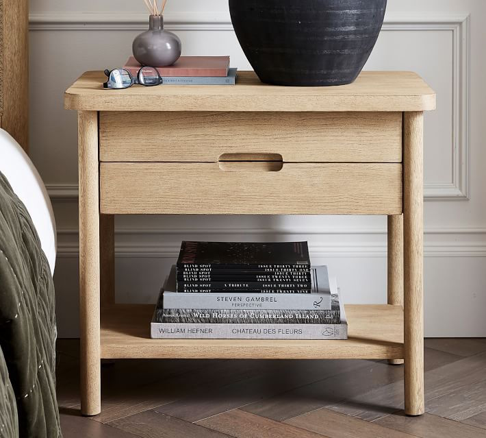 Light wood nightstand with a, indented finger groove handle between both drawers.