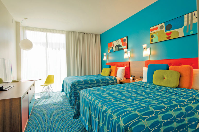 Cozy retro hotel room has blue patterned sheets and bold orange headboards.